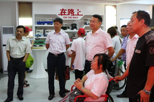 图为市残联领导与残疾人朋友参观公交博物馆