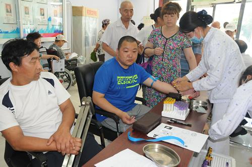 图为精准康复扶贫医疗队正在为残疾人抽取血样