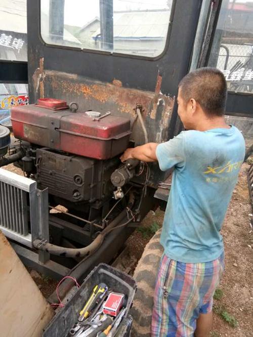 图为助残志愿者正在帮助残疾人维修农用机械