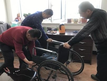 图为爱心人士维修轮椅