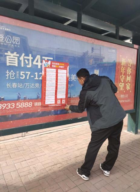 """图为群英街道西道口社区残联工作人员在公交站点张贴""""吉祥码""""海报"""